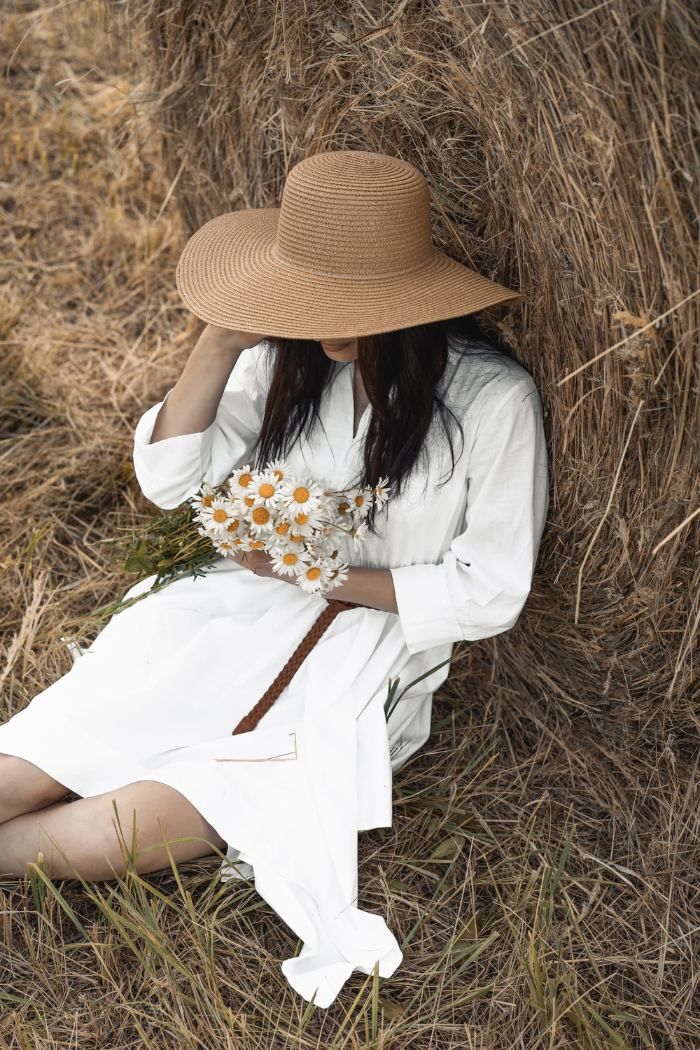 woman in white long sleeve shirt and brown hat holding white and yellow flowers