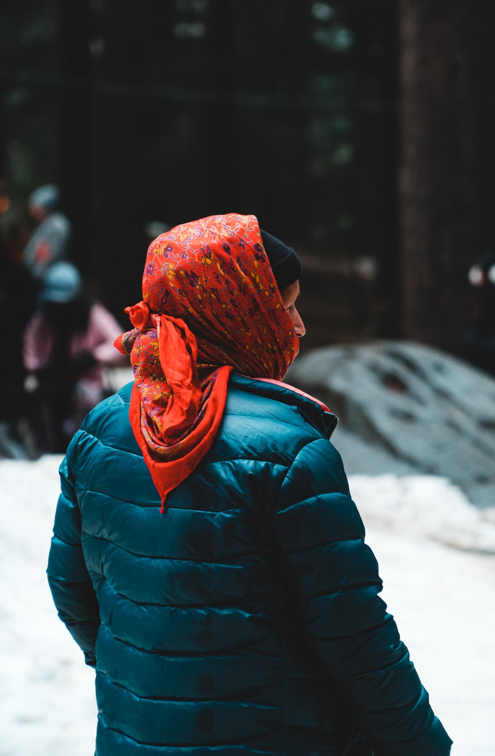 woman in blue bubble jacket and orange scarf