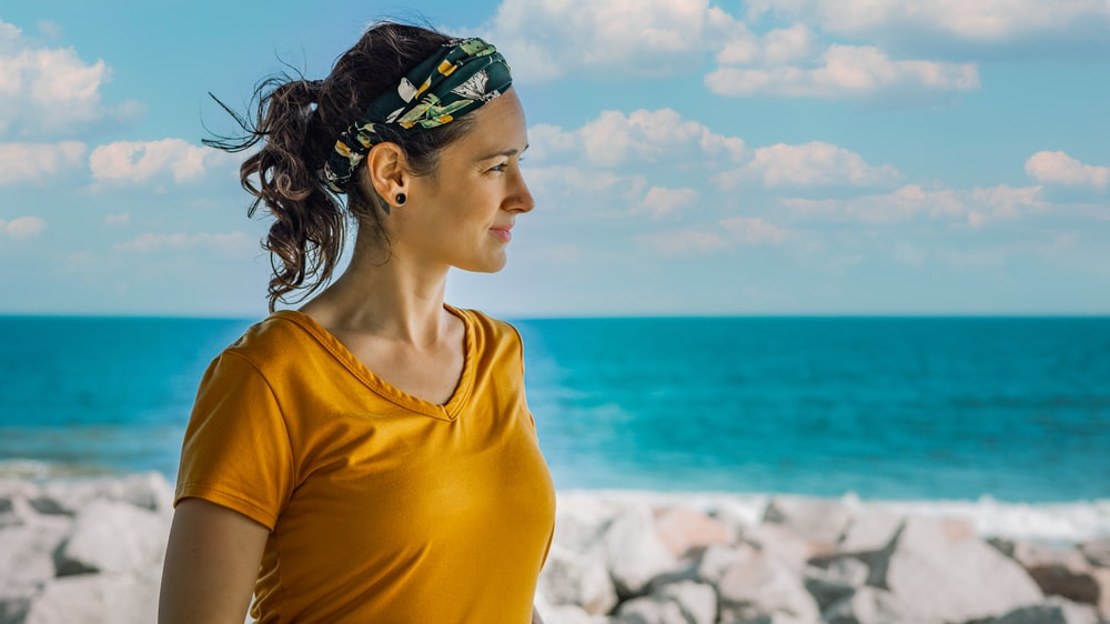 woman in yellow crew neck shirt wearing green and blue floral headband