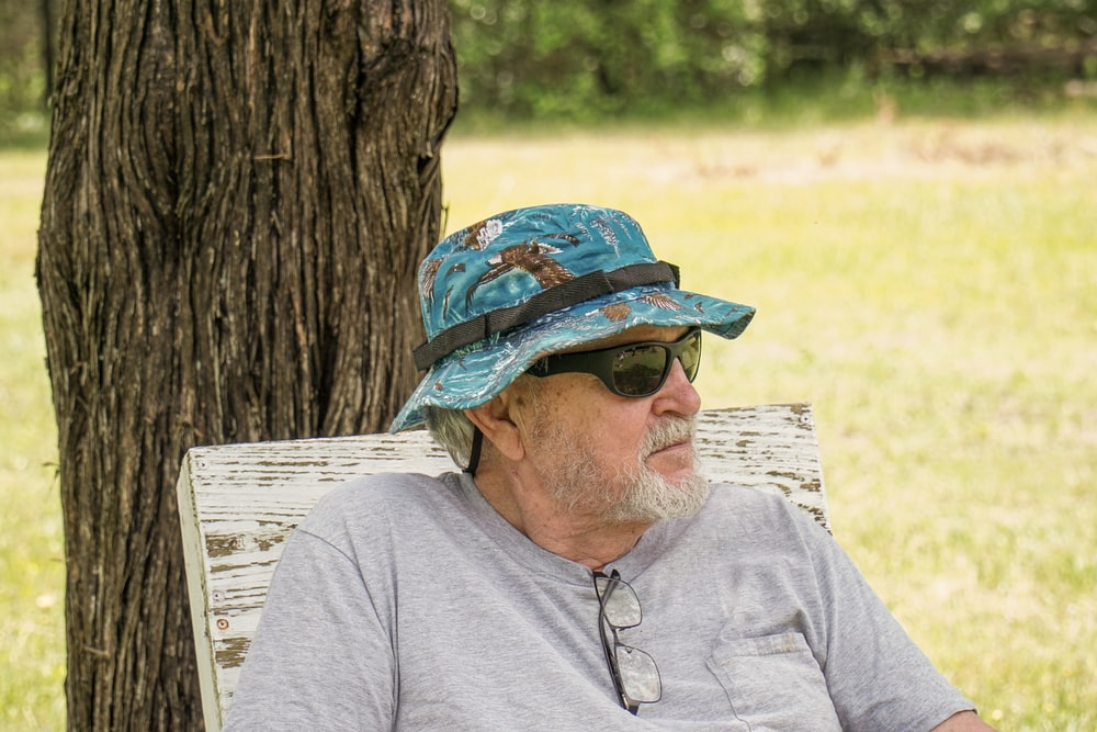 man in gray crew neck shirt wearing blue and white hat