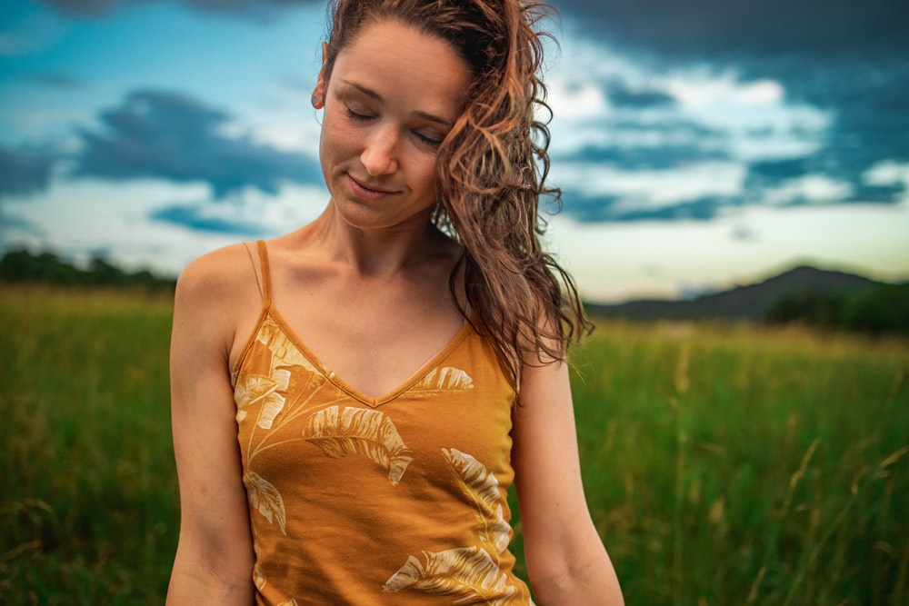 woman in yellow tank top standing on green grass field during daytime