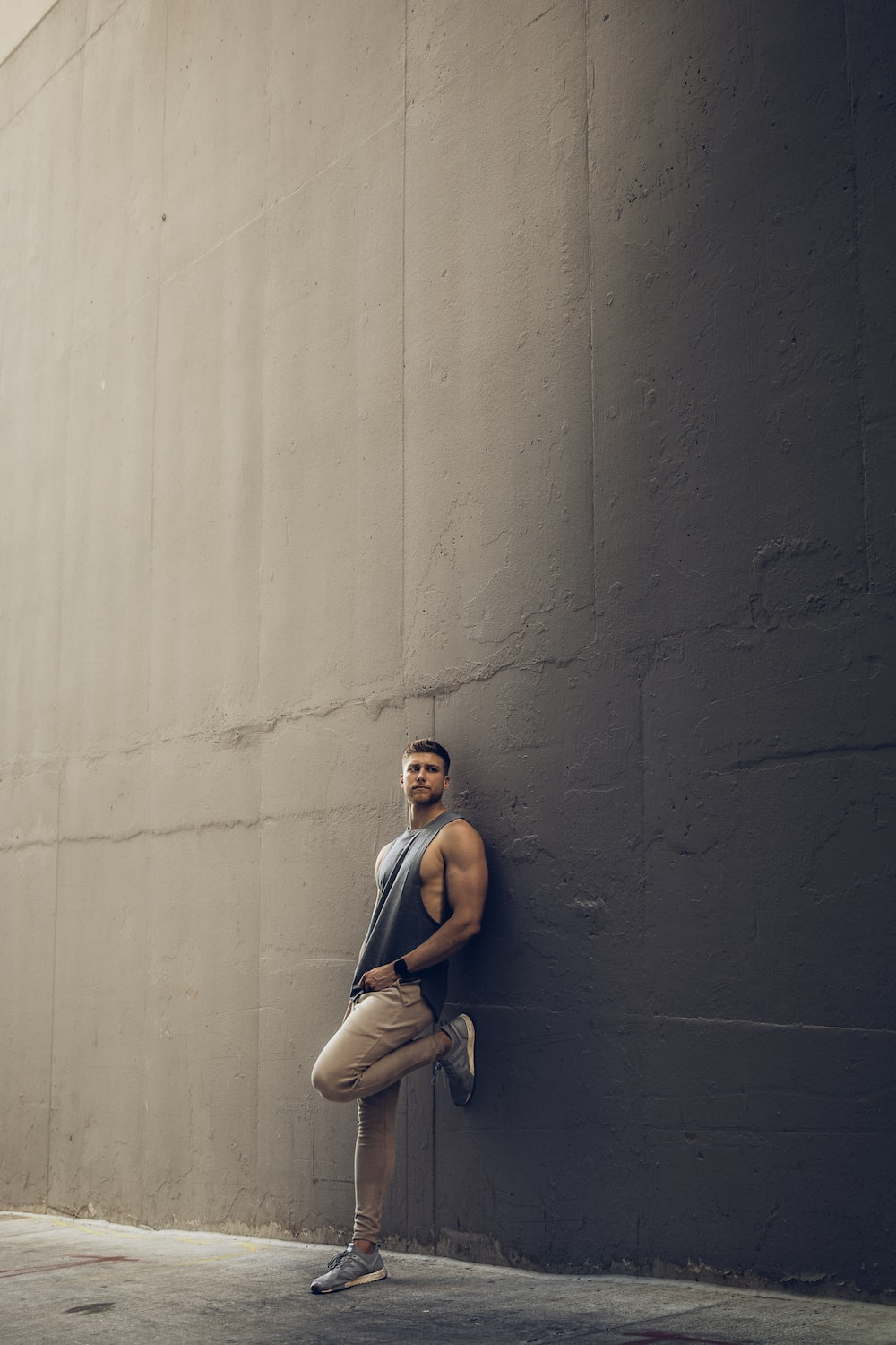 woman in blue tank top and beige pants sitting on concrete wall