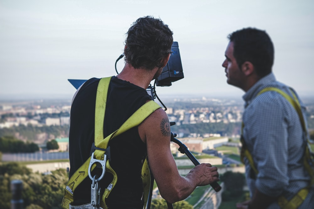 man in green and black backpack holding black camera