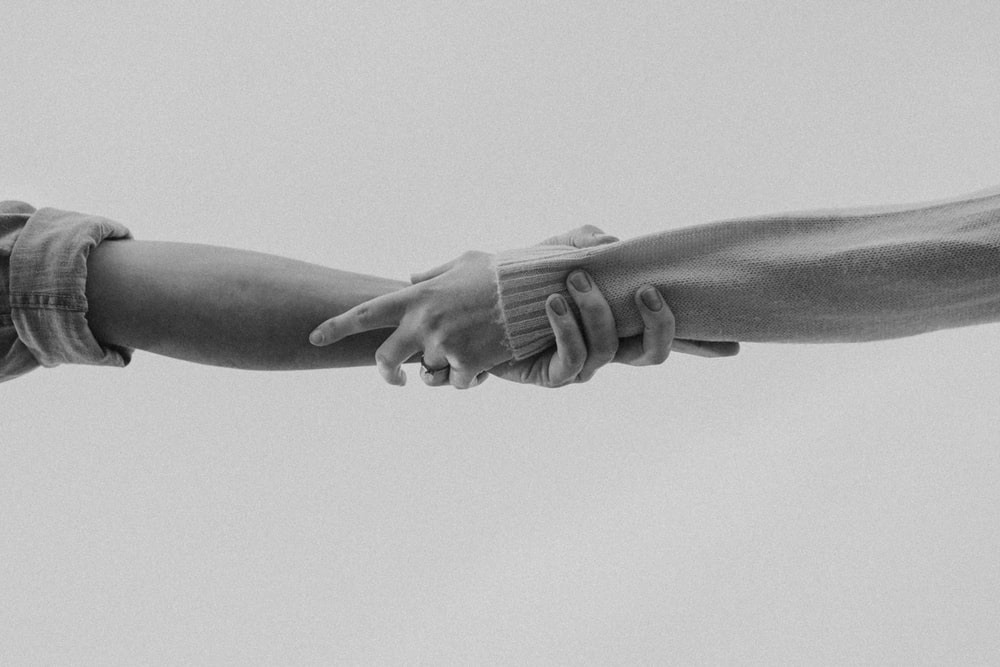 grayscale photo of person holding hands