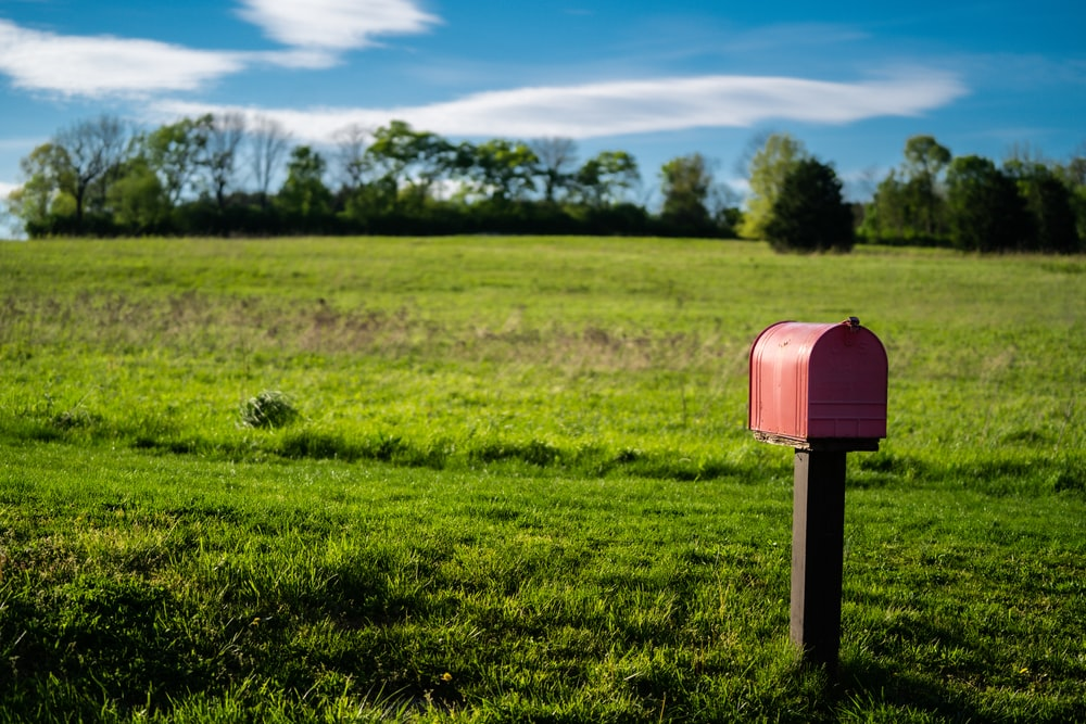 red mail box on green grass field during daytime