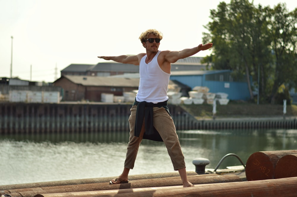 man in white tank top and brown pants jumping on brown wooden dock during daytime