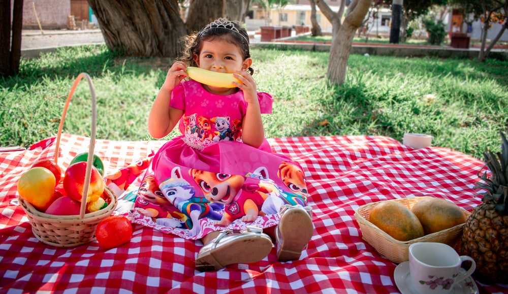 girl in pink and white floral dress eating bread