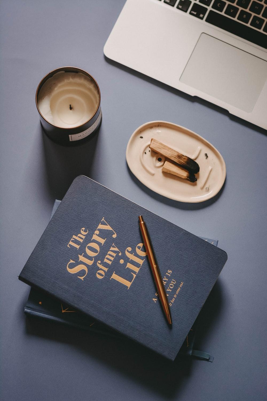 brown chopsticks on white ceramic round plate beside black book