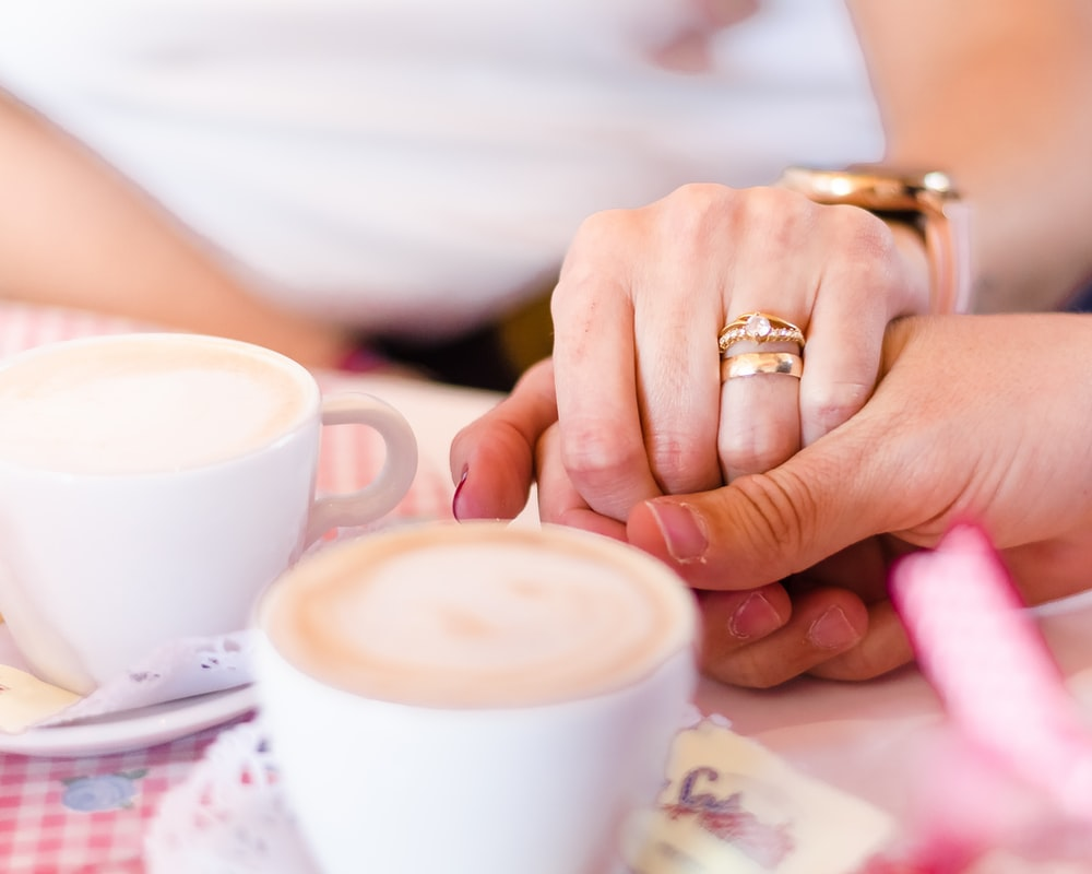 person wearing gold wedding band holding white ceramic mug