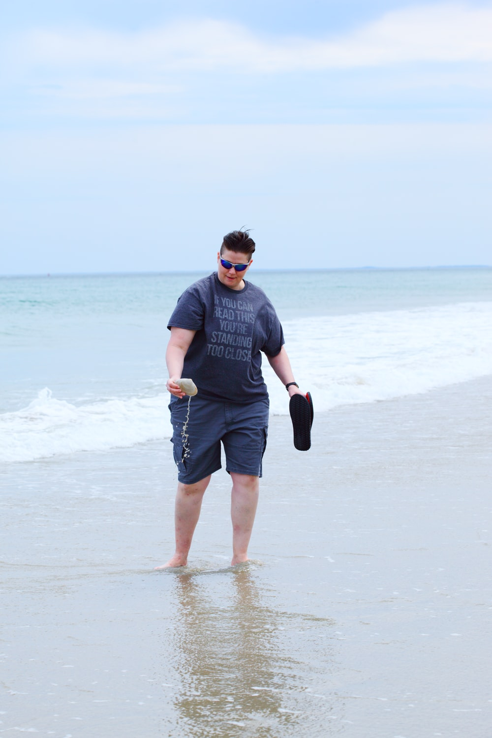 man in gray crew neck t-shirt and black shorts running on beach during daytime