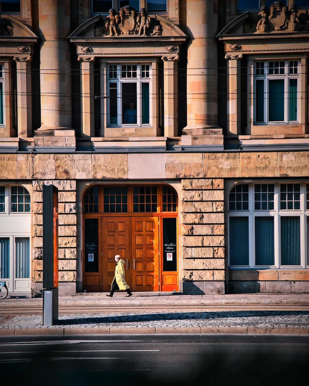 man in brown coat walking on sidewalk near brown concrete building during daytime