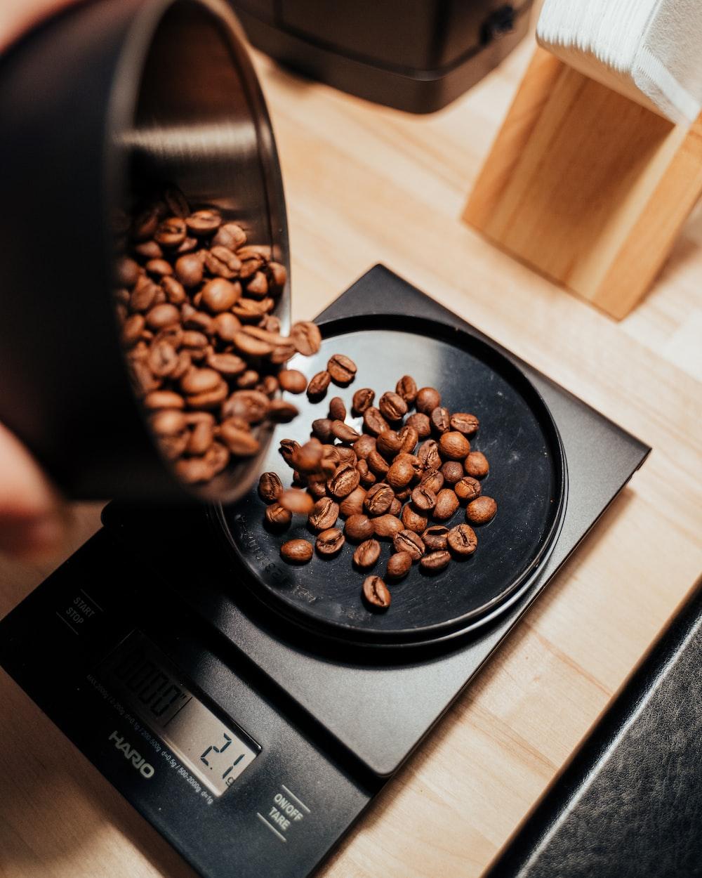 brown coffee beans on black ceramic mug