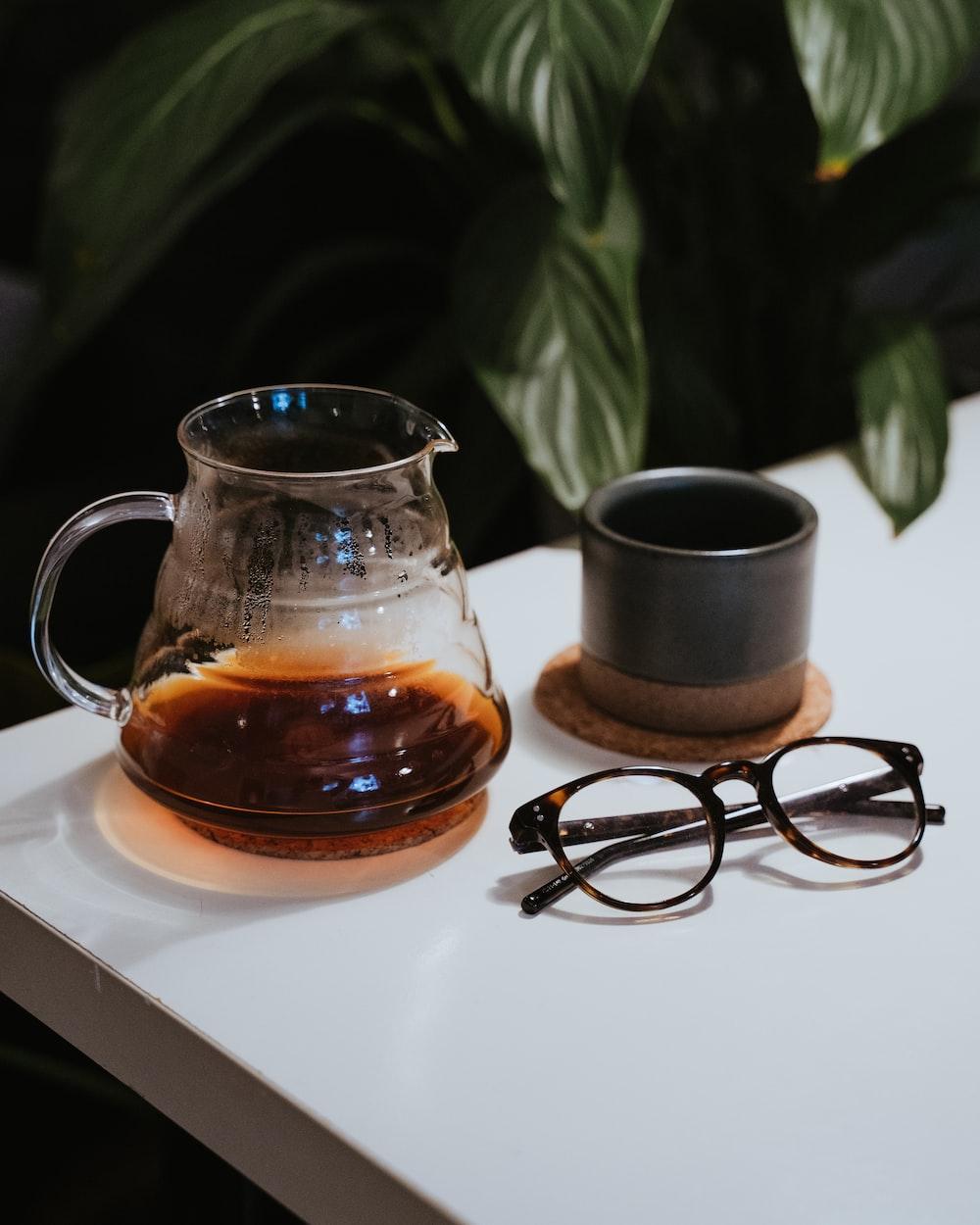 black framed eyeglasses beside clear glass mug on white table
