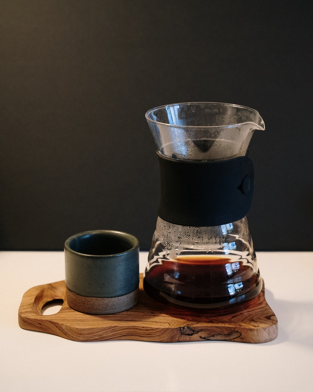 black coffee in clear glass pitcher on brown wooden coaster