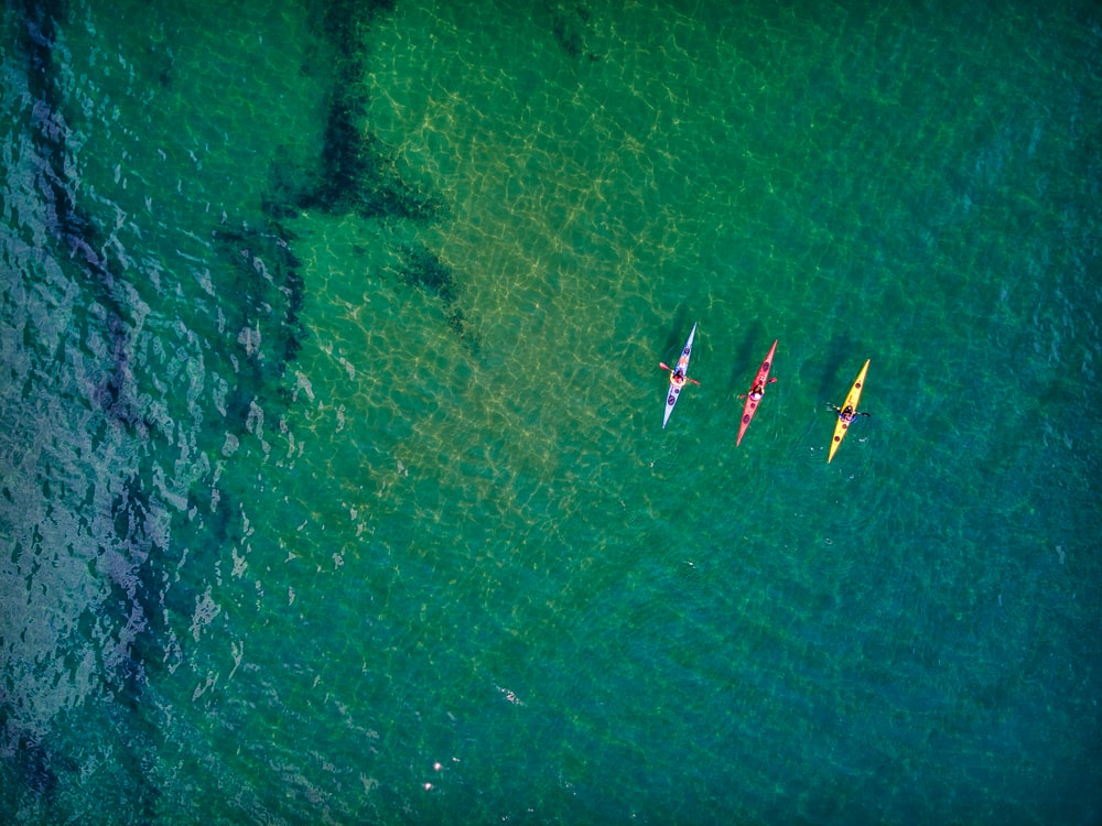 aerial view of people riding boat on sea during daytime