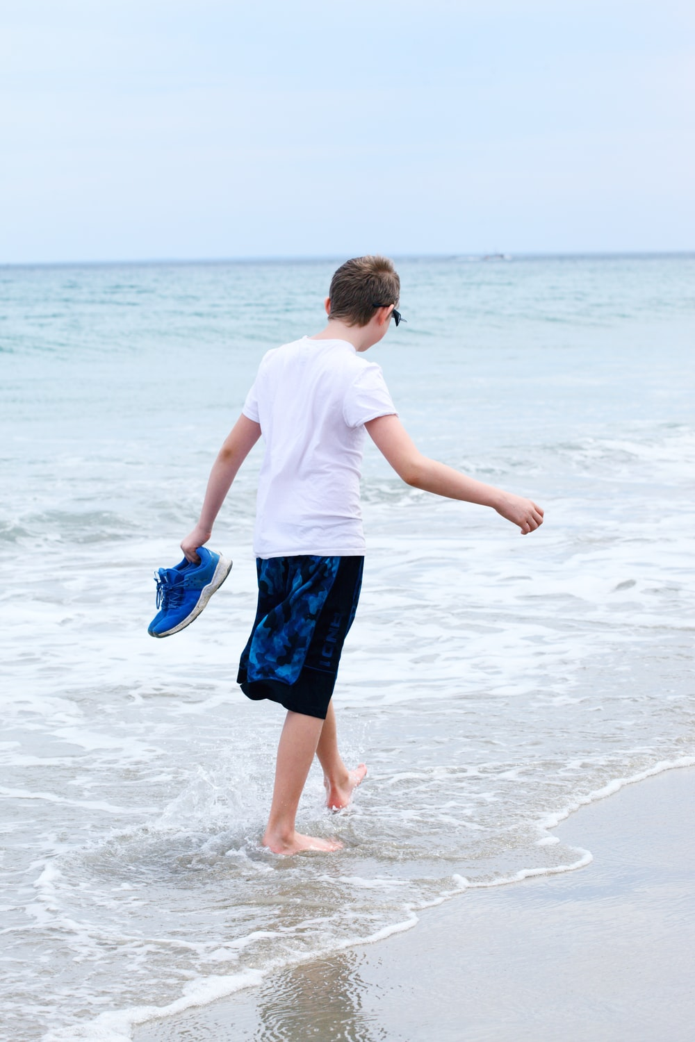 boy in white t-shirt and blue shorts running on beach during daytime