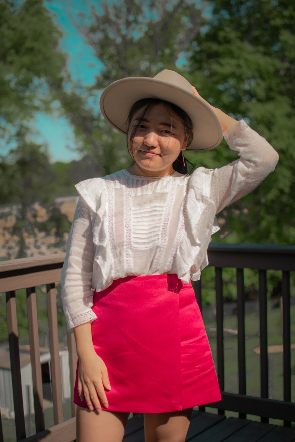 girl in white long sleeve shirt and red skirt wearing brown cowboy hat