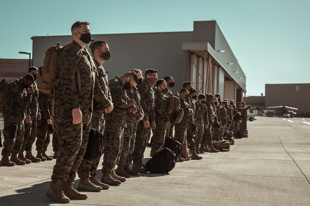 men in black and brown camouflage uniform standing on brown floor