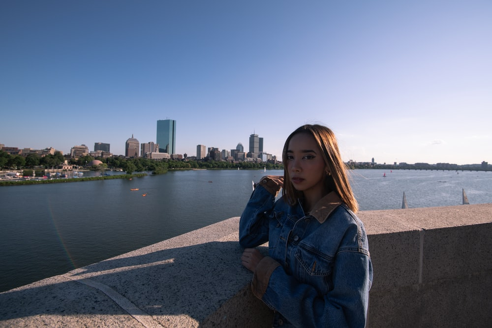 woman in blue denim jacket sitting on gray concrete pavement near body of water during daytime