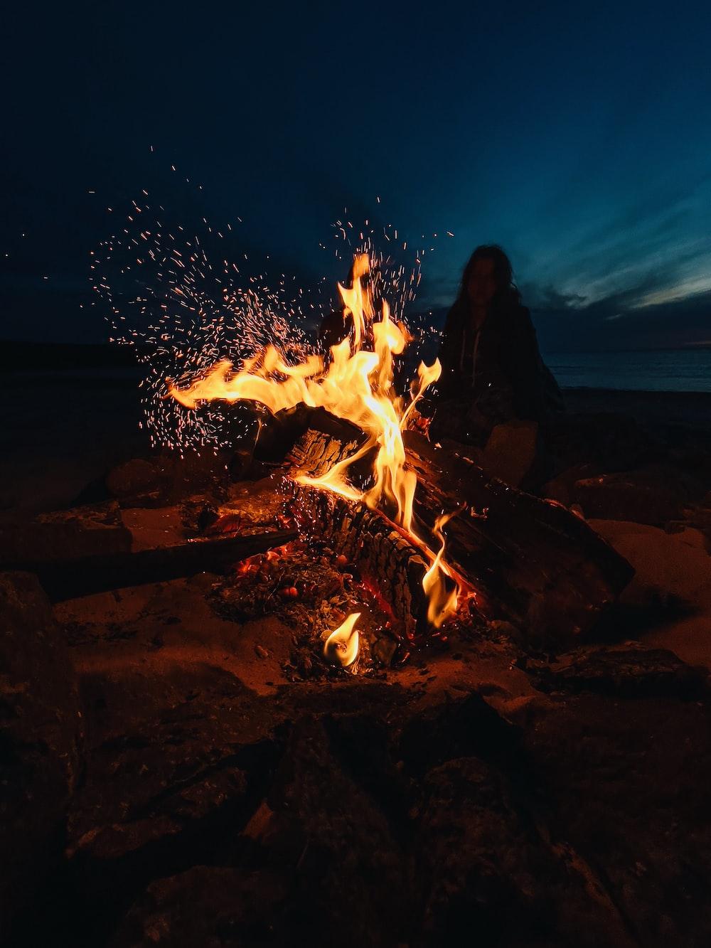 man in black jacket standing near bonfire during night time