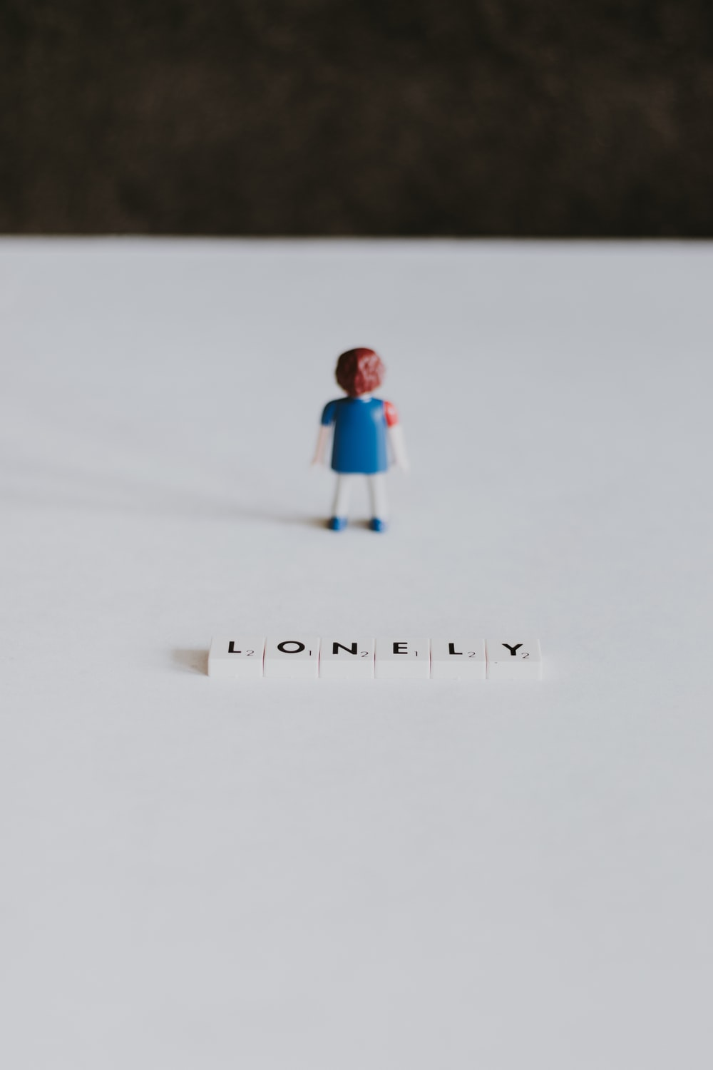 child in teal jacket and blue pants walking on snow covered ground during daytime