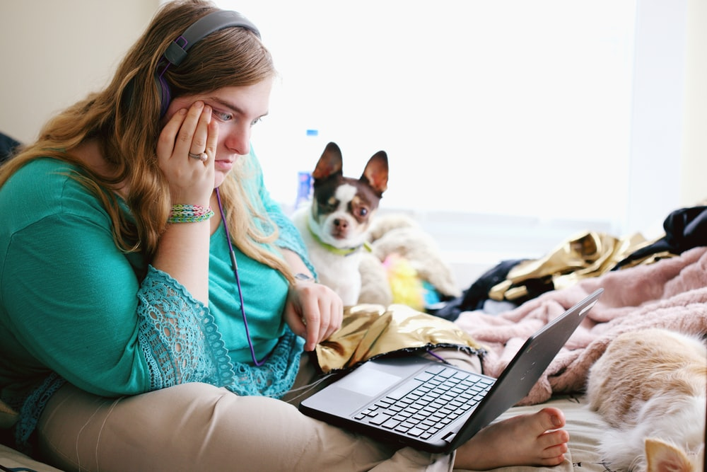 woman in teal long sleeve shirt holding black laptop computer