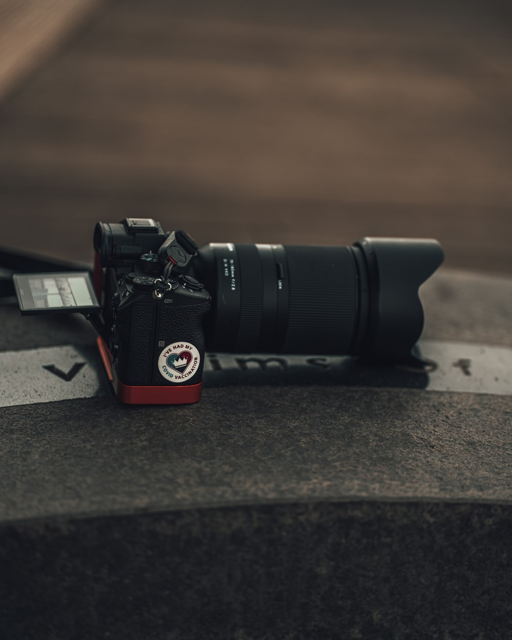 black and red dslr camera on gray concrete floor