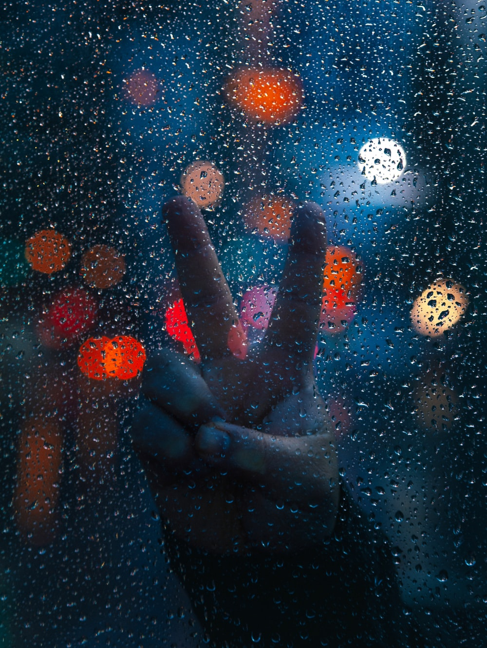 persons hand on glass with water droplets