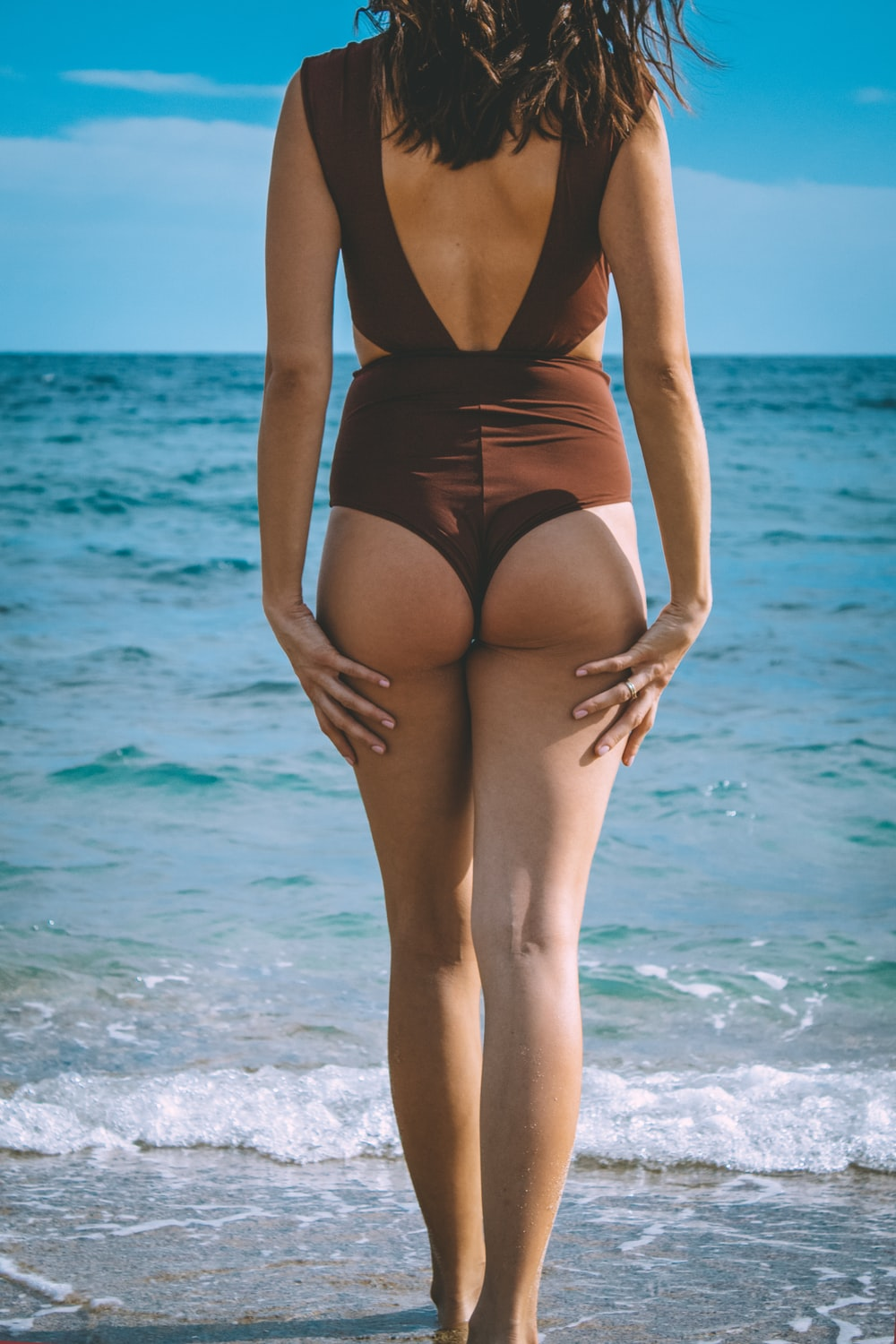 woman in black one piece swimsuit standing on beach during daytime