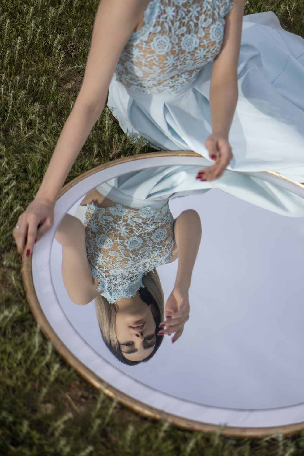 girl in white and blue floral dress lying on green grass field