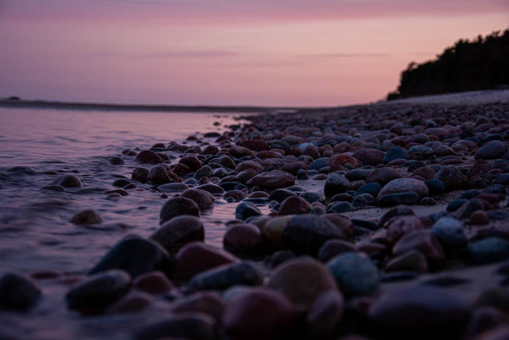 black and gray stones on seashore during sunset