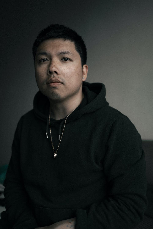 man in black hoodie wearing silver necklace