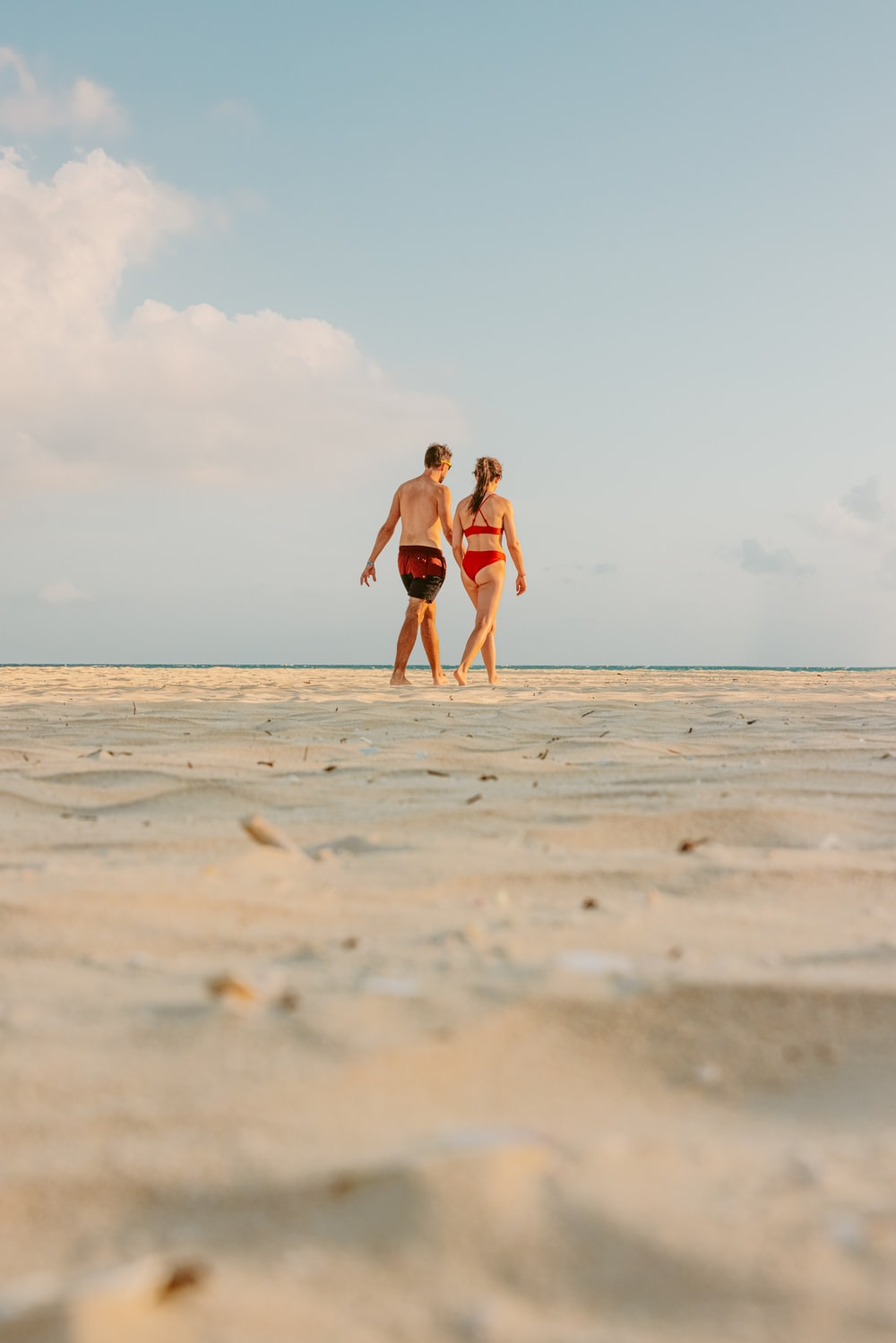 a couple walking on beach during daytime