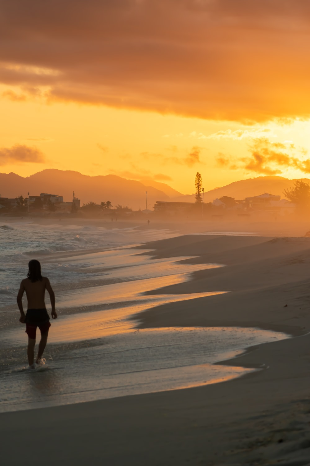 woman in black shirt walking on beach during sunset