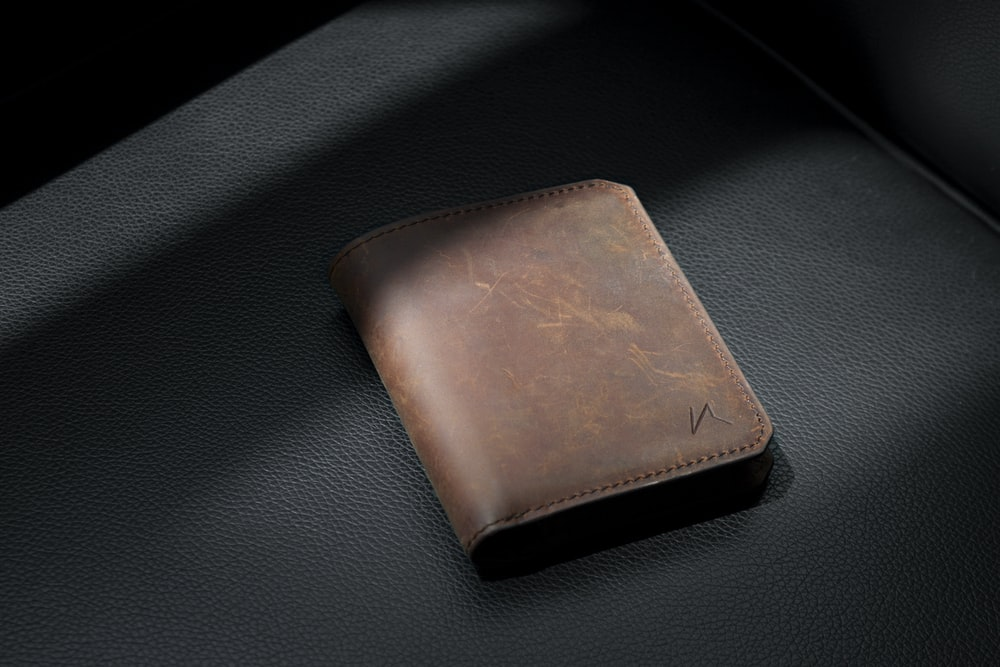 brown leather bifold wallet on black leather textile