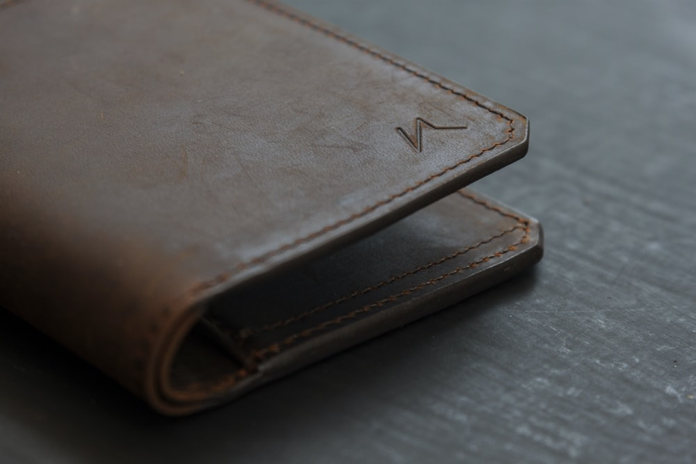 brown leather bifold wallet on gray wooden table