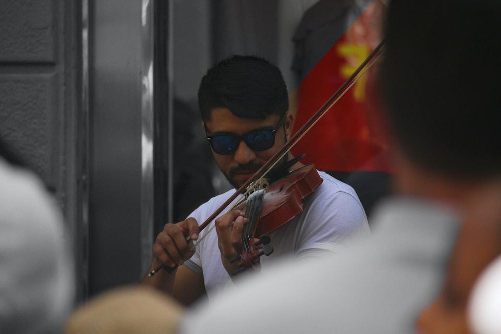 man in white shirt playing violin