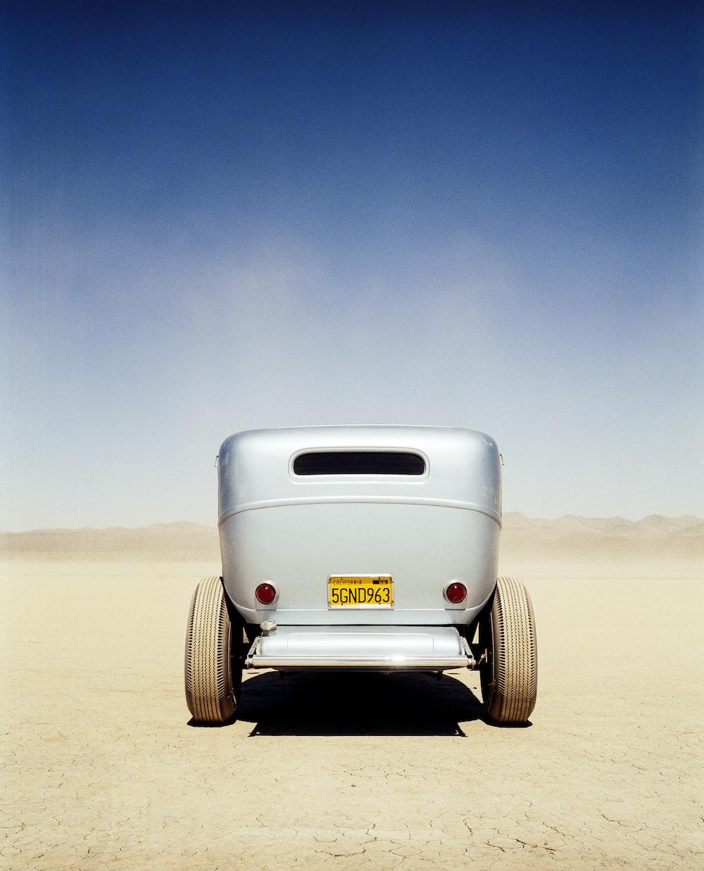 white car on brown sand under blue sky during daytime