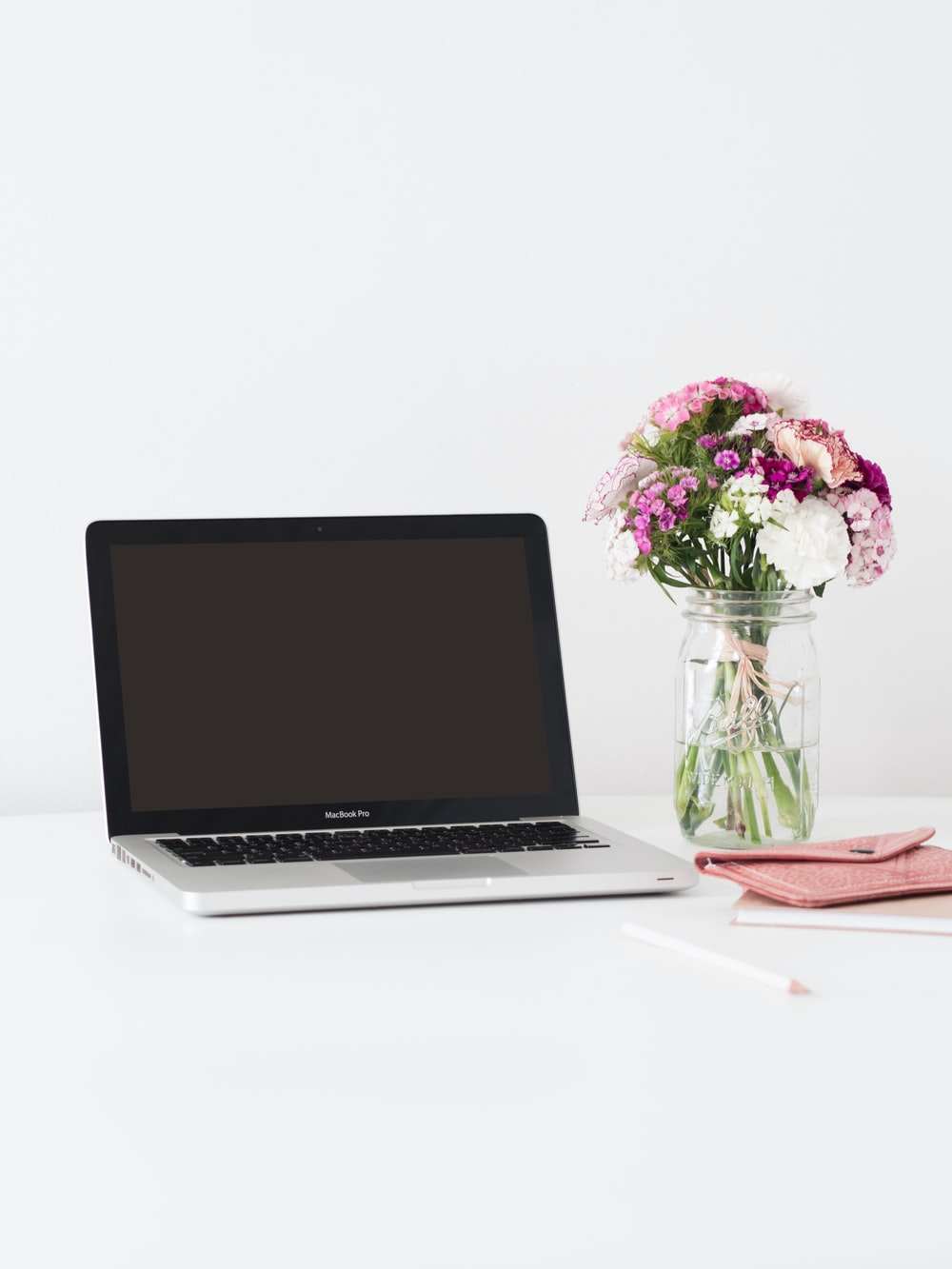 macbook pro beside pink and white flowers in clear glass vase