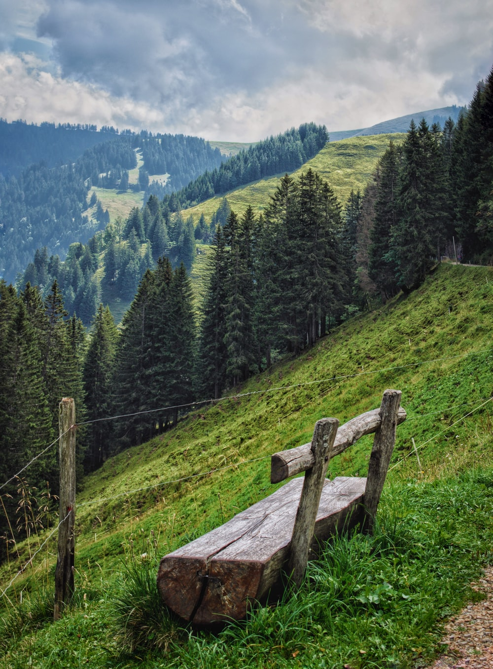 brown wooden fence on green grass field near green trees and mountains during daytime