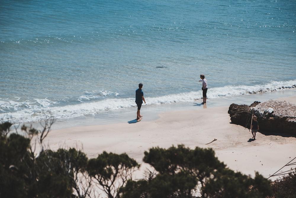 man in black jacket walking on seashore during daytime