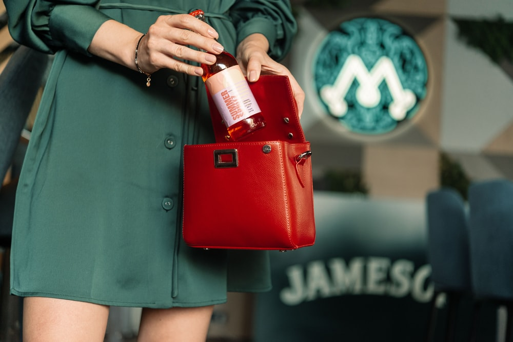 woman in green button up shirt holding red leather handbag
