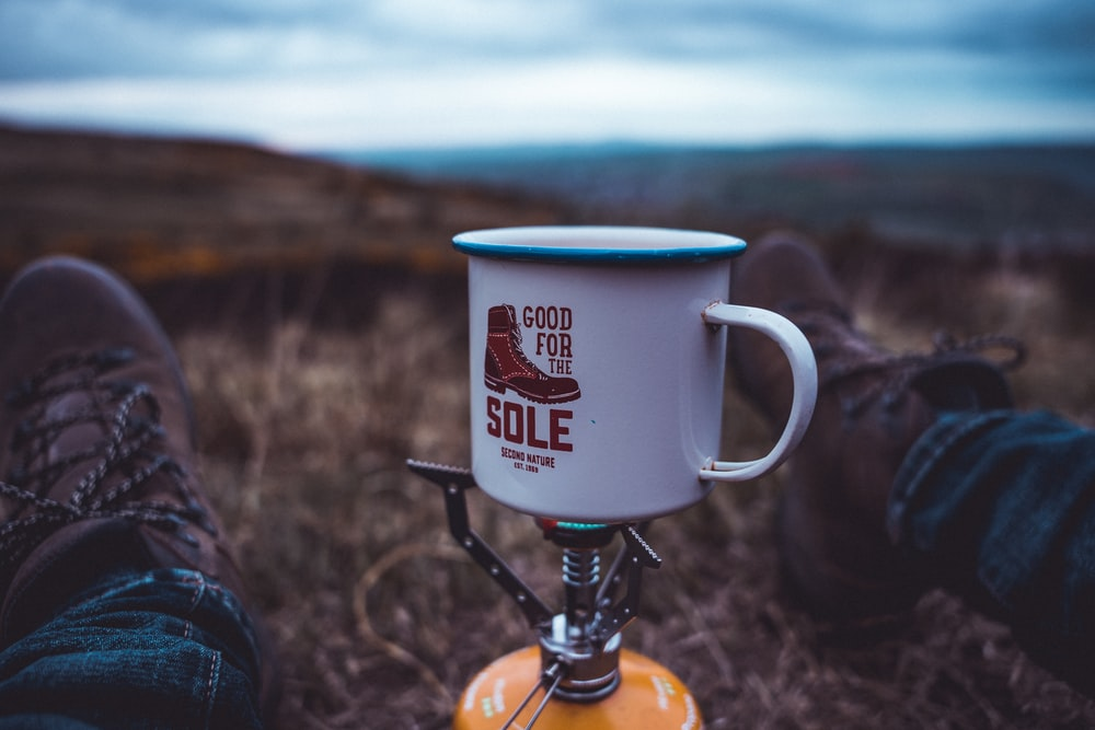 white ceramic mug on brown wooden stand
