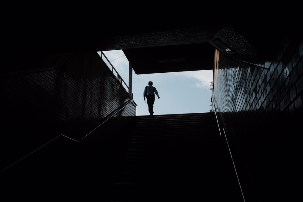 silhouette of person standing on roof during daytime