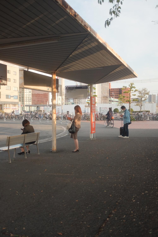 woman in black jacket and white pants walking on sidewalk during daytime