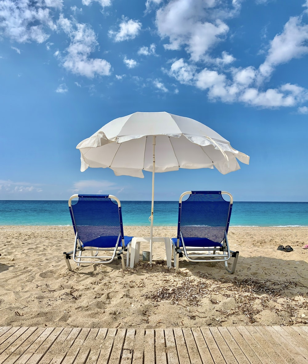 blue and white chair under white umbrella on beach during daytime