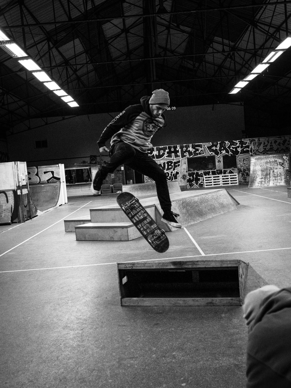man in black jacket and pants playing skateboard in grayscale photography