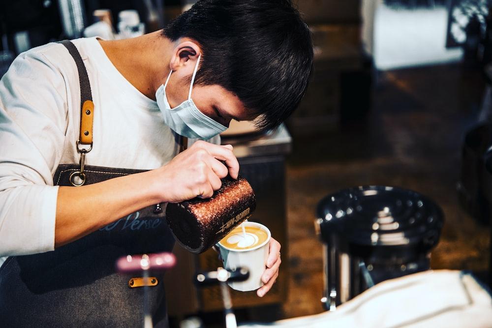 woman in white shirt holding brown ceramic mug