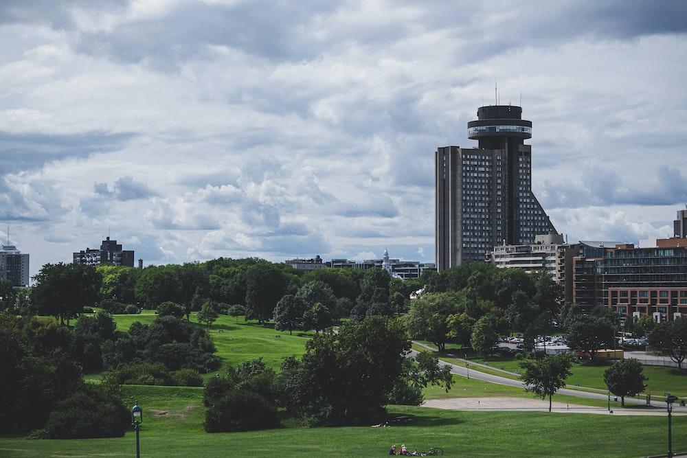 green grass field near high rise building during daytime