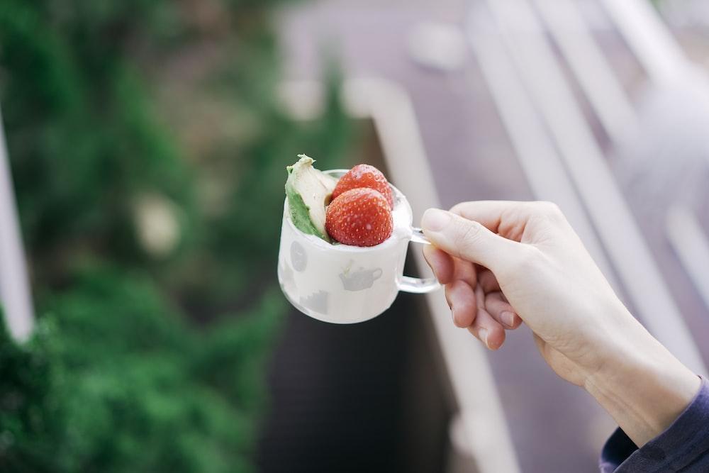 person holding white ceramic mug with strawberry and cream